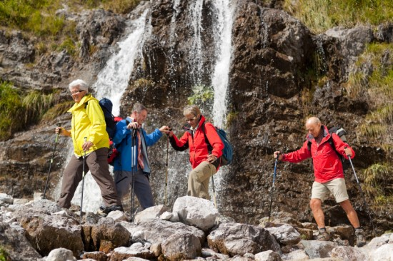 Senior hikers cross near a waterfall. Photo by Amriphoto